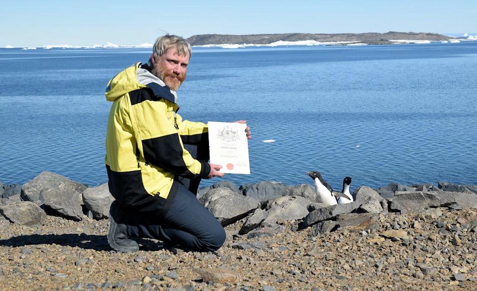 Terry, der stolz seine Bürgerschaftsurkunde zeigt, wird neugierig von der lokalen Bevölkerung, Adéliepinguinen, beobachtet. Bild: Jason Burgers/Derryn Harvie