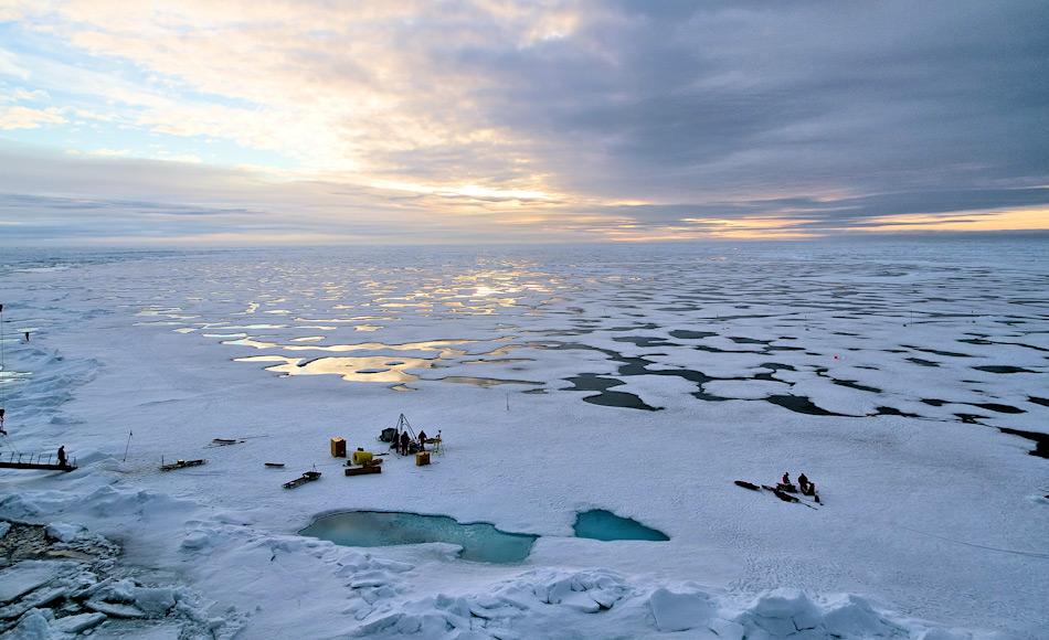 """Zur Erforschung der Schmelztümpel und Bohrlöcher, mussten die Wissenschaftler ein Camp auf dem Meereis aufschlagen. Immer in der Nähe: Der Eisbrecher """"Polarstern"""". Bild: Marcel Nicolaus"""